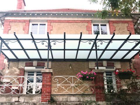Marquise-à-la-parisienne,-ossature-métallique,-motifs-en-fer-forgé,-verre-feuilleté-opale,--longueur-7,50m,-largeur-4,20-m